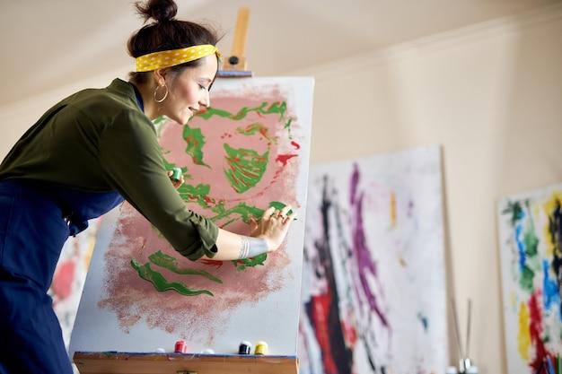 Jovem criativa de avental pintando um quadro no cavalete e aplicando tinta na tela com os dedos