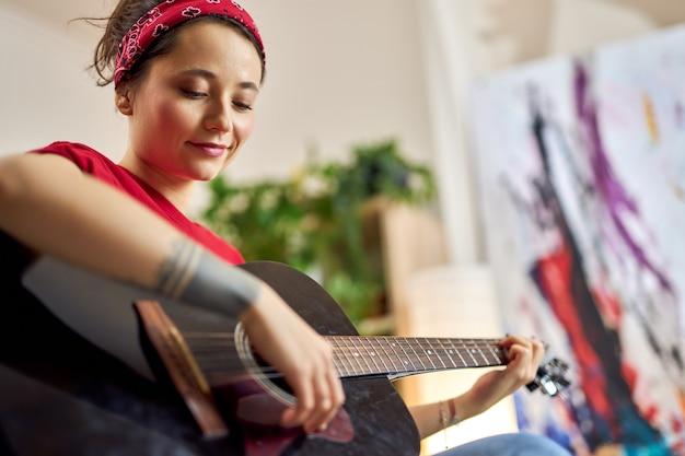 Jovem criativa tocando violão enquanto passa um tempo sozinha em casa