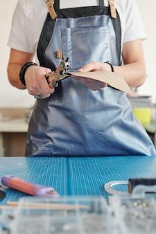Jovem criativo em traje de trabalho em pé ao lado da mesa, segurando um pedaço de couro leve e fazendo furos