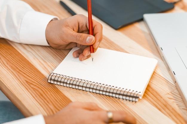 Jovem criativo fazendo anotações ou esboços de novo projeto por pensil no caderno. conceito de planejamento. feche acima do tiro. imagem enfraquecida