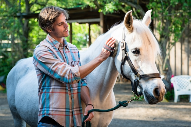 Jovem cuidando do cavalo