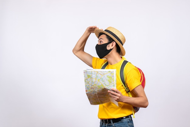 Jovem curioso de frente com máscara e mochila vermelha olhando para algo