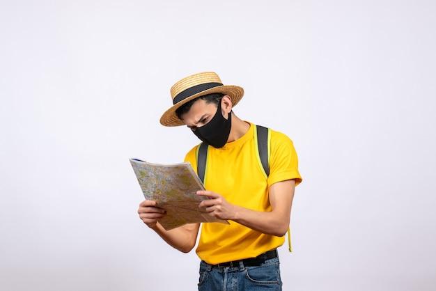 Jovem curioso de vista frontal com máscara e camiseta amarela olhando para o mapa