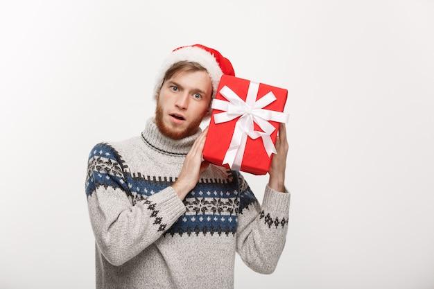 Jovem curioso feliz com barba carrega um presente e escuta dentro da caixa isolada no branco
