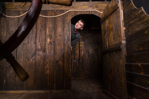 Jovem curioso homem de negócios espiando por dentro da porta da cabine de um antigo veleiro de madeira