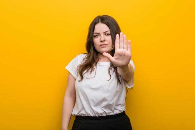 Jovem curvilínea plus size mulher em pé com a mão estendida, mostrando o sinal de stop, impedindo-o