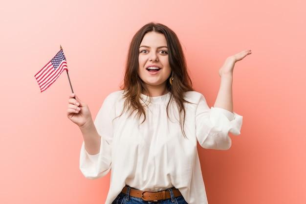 Jovem, curvilíneo, e, tamanho, mulher segura, um, estados unidos, bandeira, celebrando, um, vitória, ou, sucesso