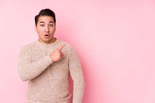 Jovem curvilíneo posando em uma parede rosa isolada apontando para o lado