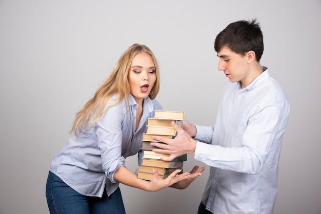 Jovem dá um monte de livro para seu parceiro na parede cinza.