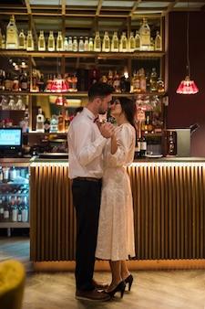 Jovem dançando com mulher magro perto de balcão de bar