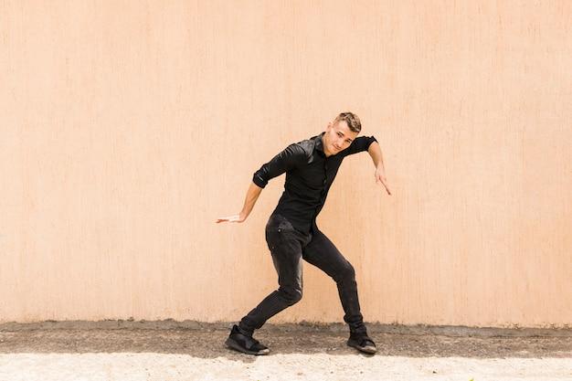 Jovem dançando hip-hop contra a parede bege