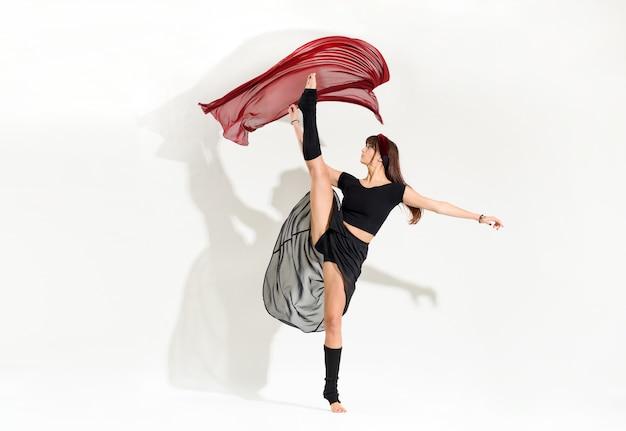 Jovem dançarina ágil executando uma pose de patinação no gelo de desenvolvimento dinâmico levantando a perna no ar enquanto ela graciosamente flutua o tecido vermelho acima de sua cabeça isolado no branco com sombra e copyspace
