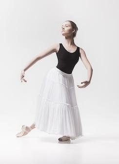 Jovem dançarina clássica dançando sobre fundo branco. projeto de bailarina.