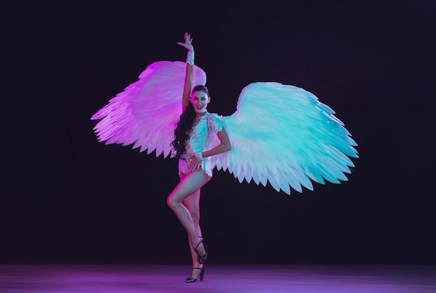 Jovem dançarina com asas de anjo branco em cores neon. modelo gracioso, mulheres dançando, posando.