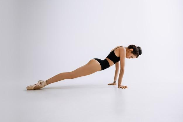 Jovem dançarina de balé em macacão preto contra a parede branca do estúdio
