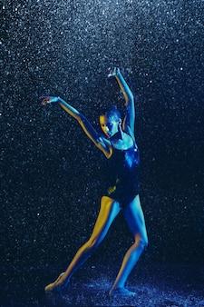 Jovem dançarina de balé realizando sob spray e gotas de água. modelo caucasiano dançando em luzes de néon. mulher atraente. conceito de balé e coreografia contemporânea.