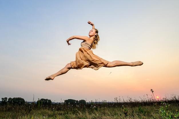 Jovem dançarina de balé se apresenta ao ar livre no pôr do sol