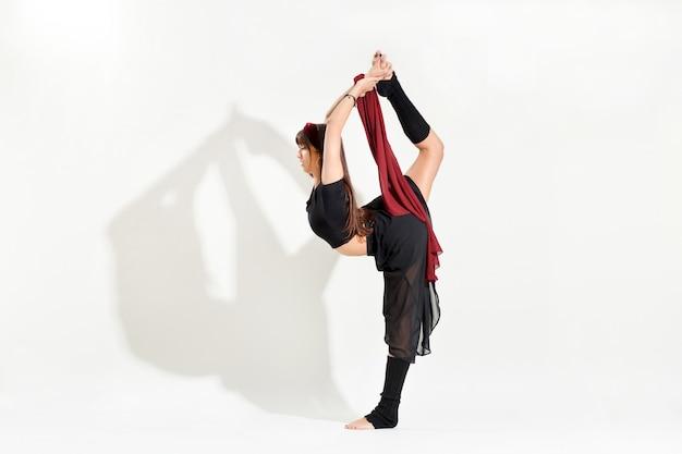 Jovem dançarina fazendo uma pose de biellman de patinação no gelo se esticando para segurar o pé enquanto se equilibra em uma perna em uma vista lateral isolada no branco com sombra e copyspace