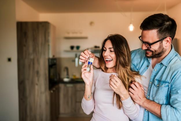 Jovem dando chaves de um novo lar para sua esposa.