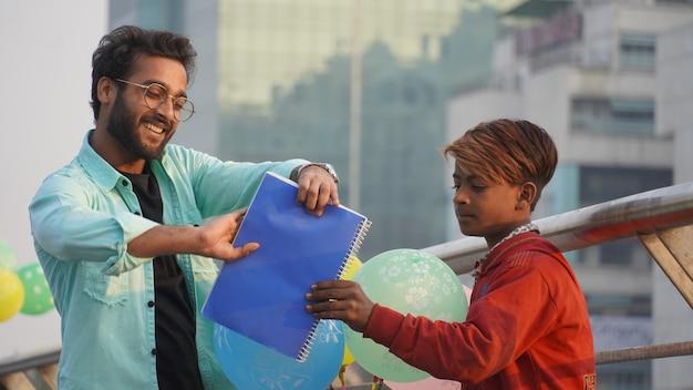 Jovem dando livros para criança pobre para estudar