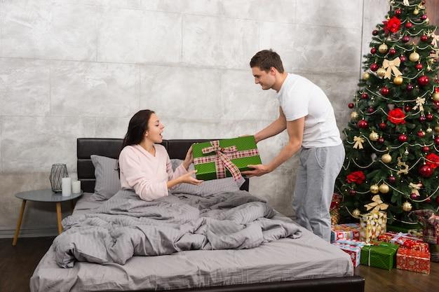 Jovem dando um presente para sua namorada surpresa, enquanto ela está sentada em uma cama de pijama no quarto em estilo loft com árvore de natal repleta de presentes