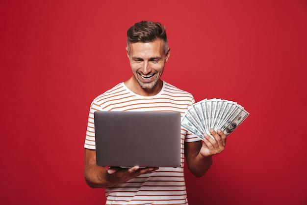 Jovem de 30 anos em uma camiseta listrada sorrindo enquanto segura um leque de notas de dinheiro e laptop isolado no vermelho