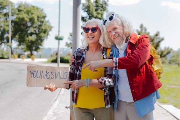 Jovem de alma. homem idoso positivo apontando para a placa enquanto pedia carona com sua esposa
