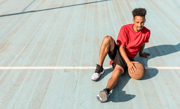 Jovem de alto ângulo em um campo de basquete com espaço de cópia