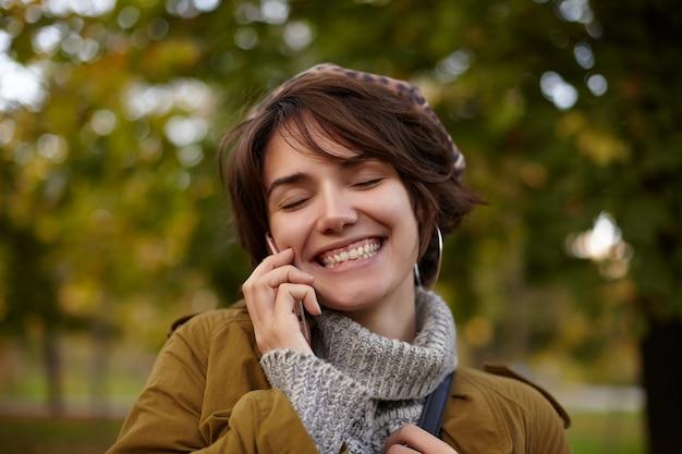 Jovem de aparência agradável, alegre adorável fêmea de cabelos curtos, mantendo os olhos fechados enquanto sorri feliz durante uma conversa agradável ao telefone, em pé sobre o parque desfocado em roupas aconchegantes e quentes