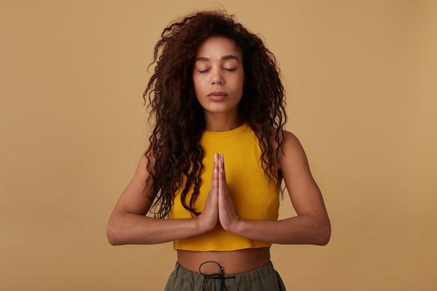 Jovem de aparência agradável, calma, morena, cacheada, morena, mulher, mantendo os olhos fechados enquanto medita e levantando as mãos postas, isolado em bege