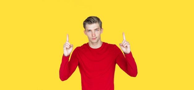 Jovem de aparência europeia em um fundo amarelo. levanta dois dedos indicadores. copie o espaço