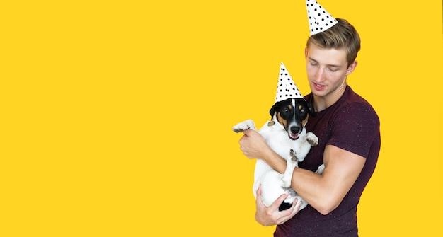Jovem de aparência europeia em um fundo amarelo. segurando um cachorro jack russell. conceito de aniversario