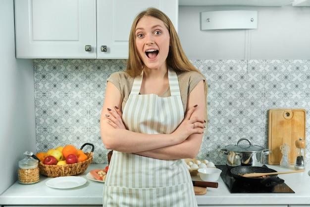 Jovem de avental com braços cruzados em casa na cozinha