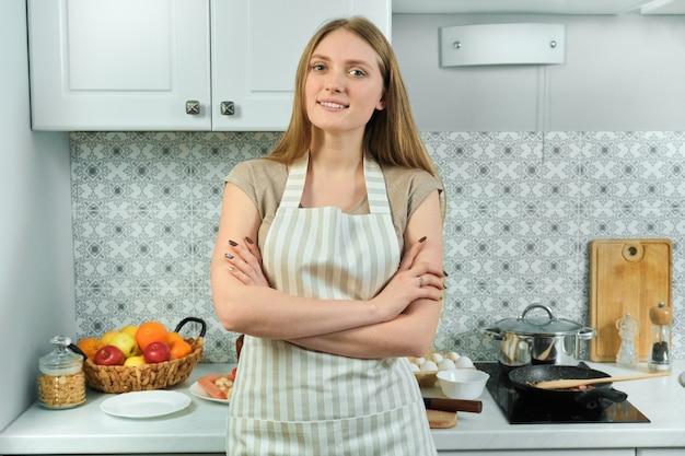 Jovem de avental, feminino em pé na cozinha com os braços cruzados