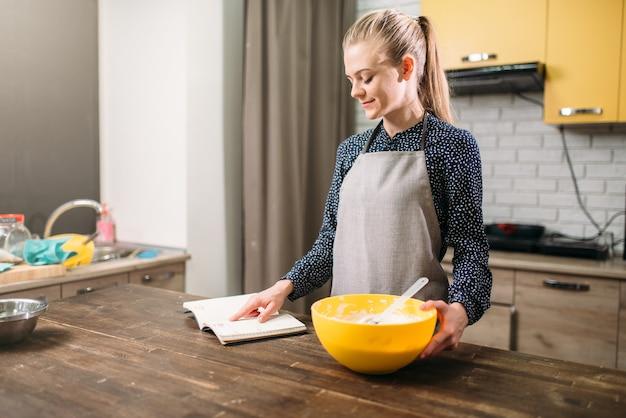 Jovem de avental lendo a receita do bolo. preparação de sobremesa doce para cozinhar
