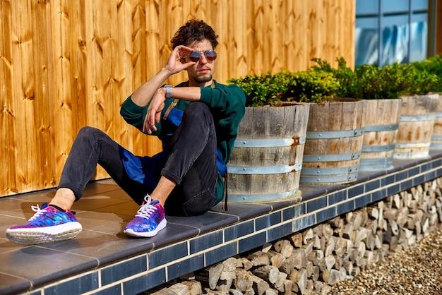 Jovem de avental sentado no terraço de uma casa de madeira.