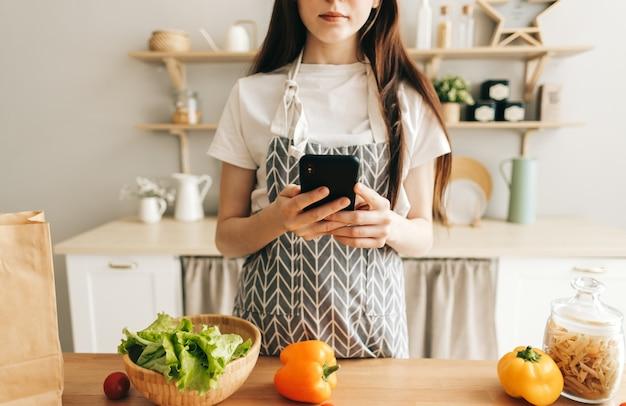 Jovem de avental usando smartphone na cozinha