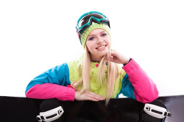 Jovem de beleza em terno de esqui e óculos de esqui sente-se com prancha