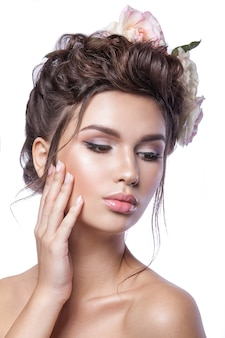 Jovem de beleza, pele limpa, bela maquiagem, tranças de penteado e flores rosas no cabelo.