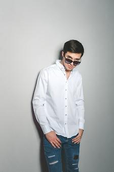 Jovem de bermuda e camisa branca está sorrindo em pé perto da parede com óculos