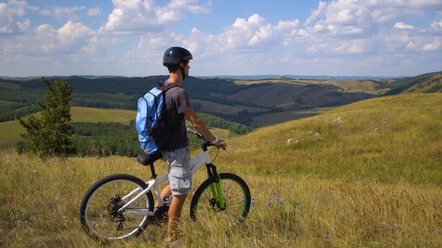 Jovem de bicicleta entre a colina verde contra um céu com nuvens