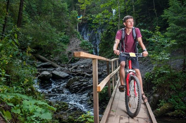 Jovem de bicicleta na floresta