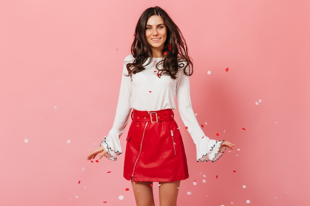 Jovem de blusa branca e saia longa vermelha está sorrindo no contexto de confetes caindo.