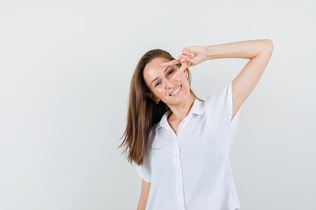 Jovem de blusa branca mostrando o gesto do vencedor em um olho e parecendo alegre