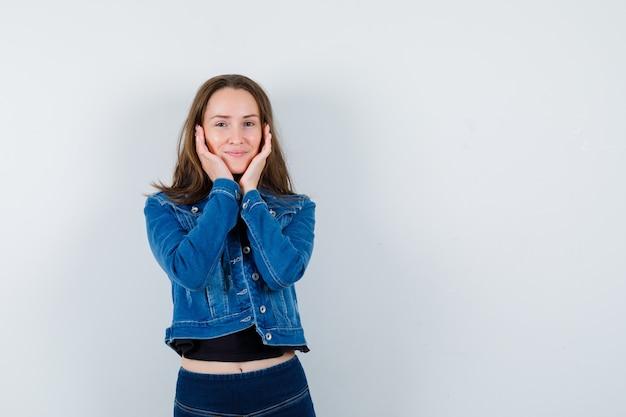 Jovem de blusa, jaqueta de mãos dadas nas bochechas e olhando graciosa, vista frontal.