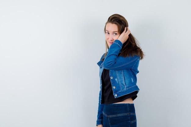 Jovem de blusa, jaqueta, segurando a mão na cabeça e olhando encantadora, vista frontal.