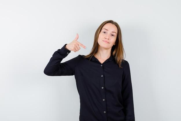 Jovem de blusa preta, apontando para si mesma com o dedo indicador e olhando feliz, vista frontal.