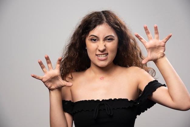 Jovem de blusa preta com cabelo encaracolado posando. foto de alta qualidade