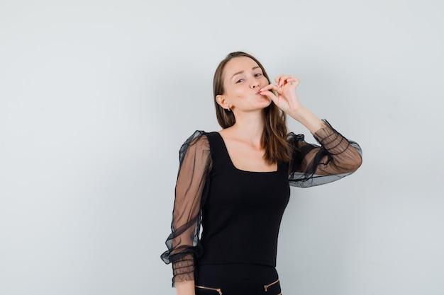 Jovem de blusa preta e calça preta, mostrando um gesto delicioso e parecendo satisfeita, vista frontal.