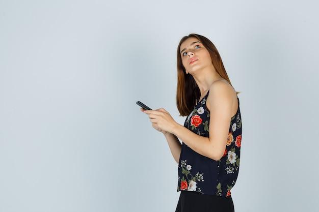 Jovem de blusa segurando o smartphone enquanto olha para cima e parece pensativa.